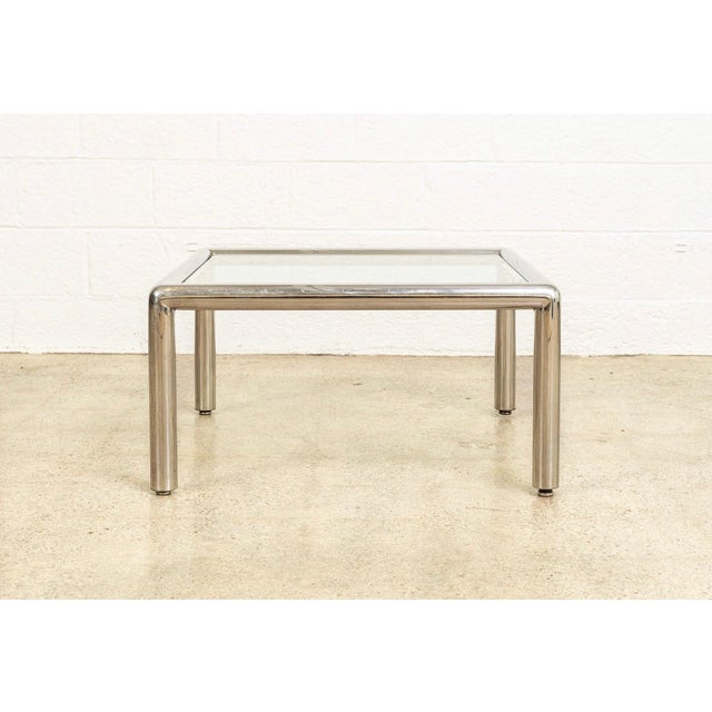 This vintage mid century modern chrome and glass coffee table was designed by John Mascheroni in 1967. It features a...