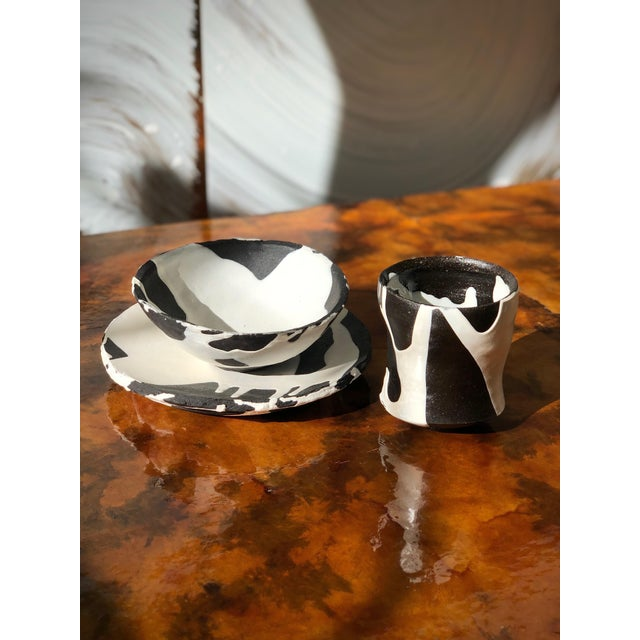 Studio ceramic table ware set made of black clay, with a white glazed paint. Each piece has the artist's signature/mark on...