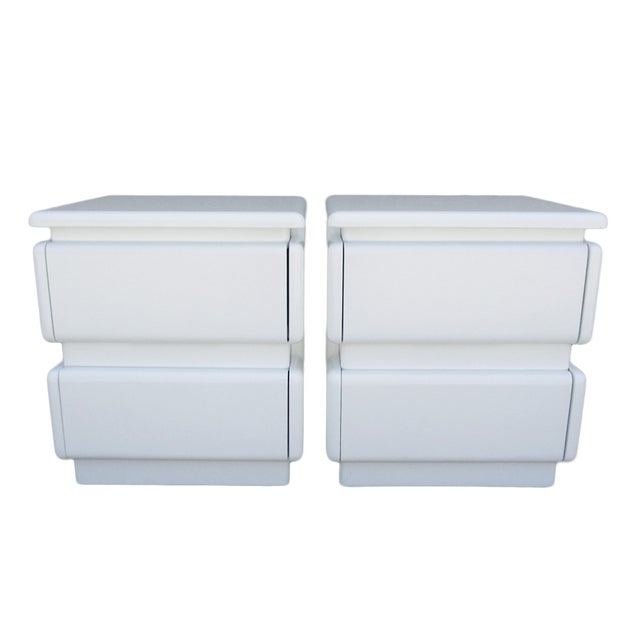 These graphic pair of night stands in white lacquer feature two drawers. Perfect modern accent for your bedroom!