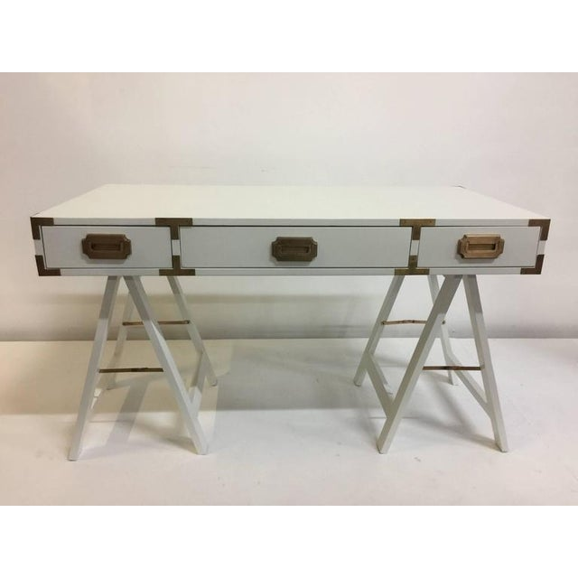 Lacquered in pristine white matte finish, this Campaign style desk sits upon trestle style sawhorse bases with original...