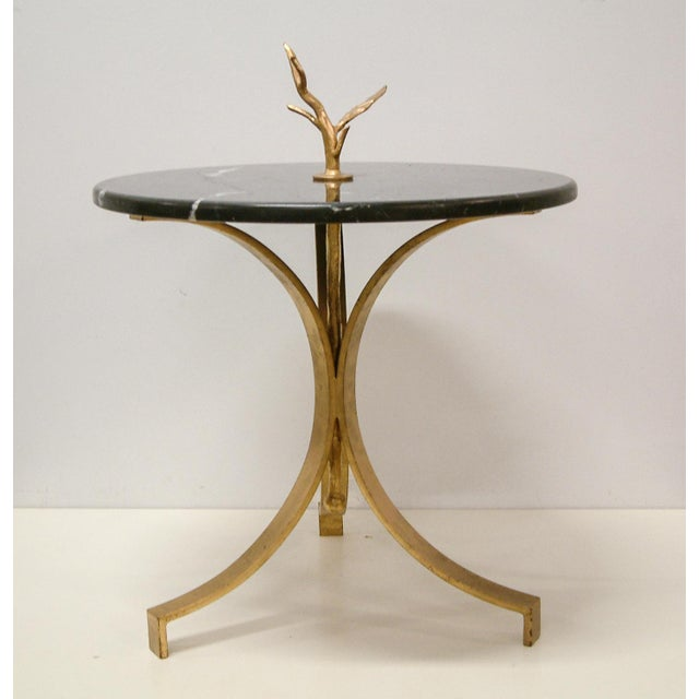 Custom design and hand fabrication of forged and gilt steel occasional table with round black marble top.