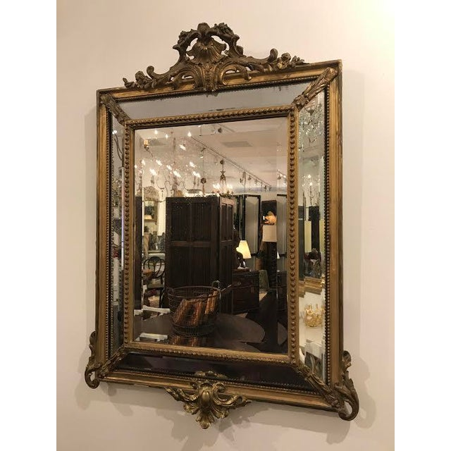 A fine antique Régence style giltwood mirror created in the pareclose design. In the late 19th century, in order to...