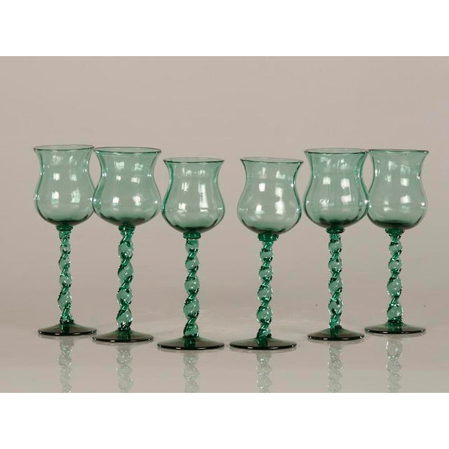 A set of six tall hand blown glass drinking vessels from France c.1875 each with a ribbon twist stem and flared rim with...