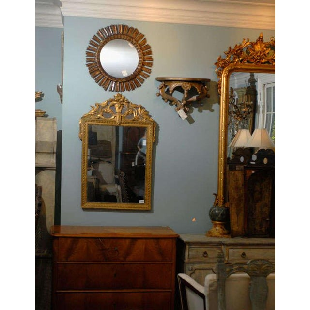 A French gilded and painted wooden mirror from the 19th century. This French mirror from the late 19th century features a...