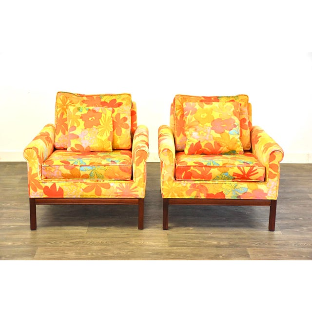 A pair of mid century modern flower pattern lounge chairs with walnut bases. Upholstery in usable condition. Seat height...