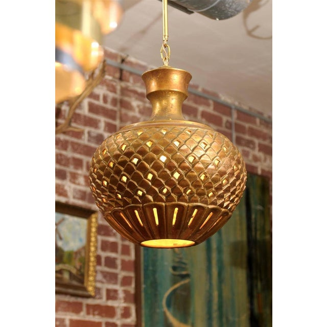 Mid Century hanging lantern or globe in the Hollywood Regency style, made of plaster with raised and pierced designs, and...