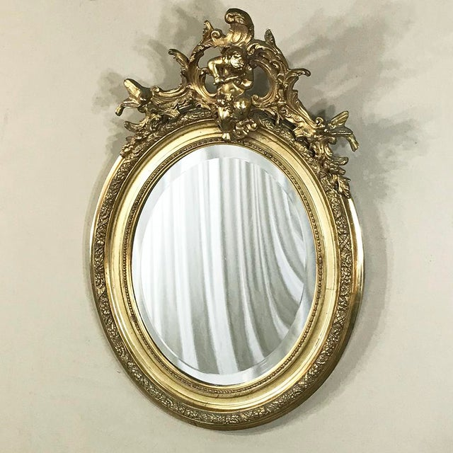 19th Century French Louis XV Gilded Mirror with Cherub features elaborate detail all around, especially on the crown which...
