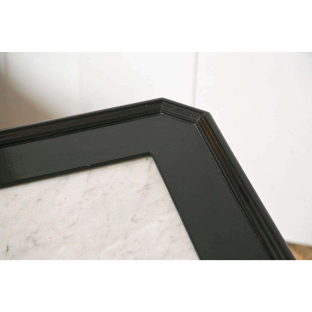 An ebonized and bronze mounted square coffee low table. The bronze sabot feet supporting a set of tappering legs. The...