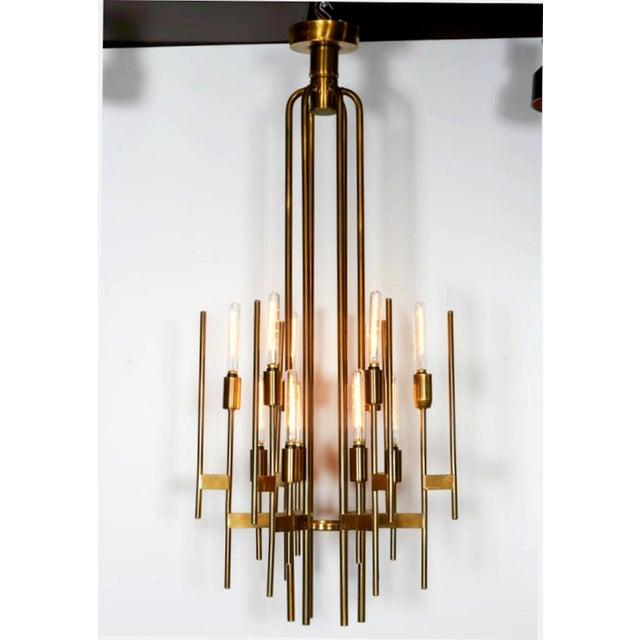 Italian Mid Century Modern sculptural brass chandelier, by Gaetano Sciolari , Italy, 1960s. Art Deco-inspired design. 12...