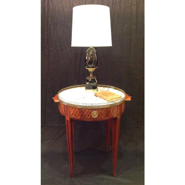Intricate inlaid French 19th century Bouillotte table with marble top, bronze gallery and two candlestick slides.
