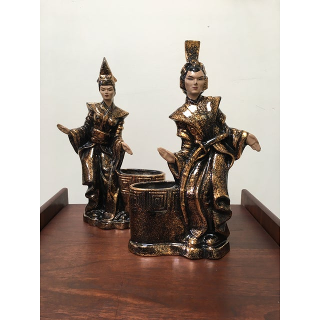 This pair of ceramic figurines with black and gold enamel. Aged just right. Bottom of one figure has slight sticker...