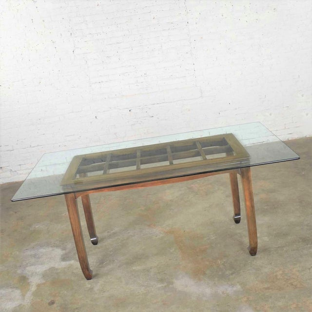 Handsome Chinoiserie chow leg walnut color finish dining table with glass top. It is in wonderful vintage condition. We...