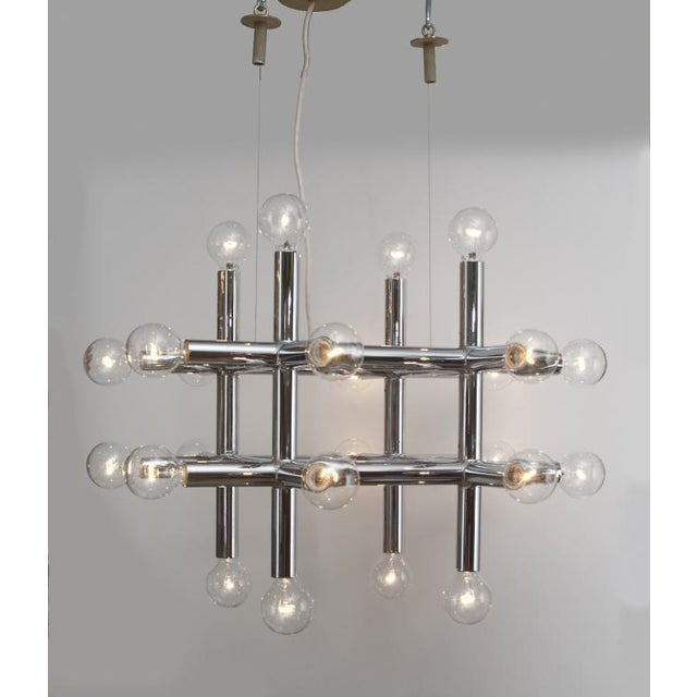 A geometric chandelier comprising eight chrome steel tube arms in a tic tac toe formation, each with a bulb at both ends....