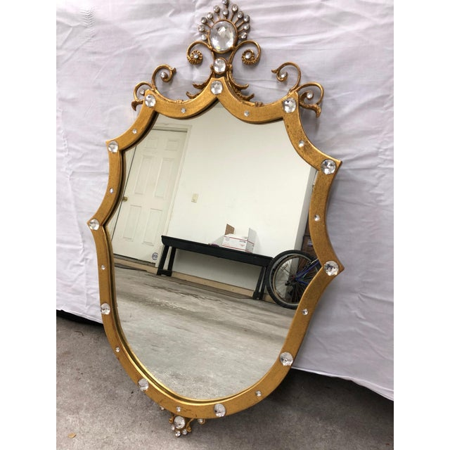 This French Style shield mirror dons an antique gold painted finish along with strategically placed crystals around its...