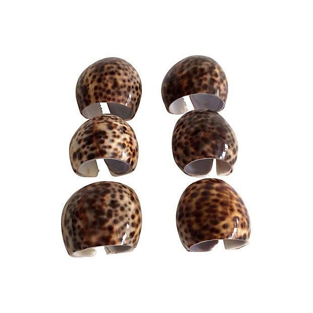 A set of six whimsical seashell napkin holders with a natural animal print pattern.
