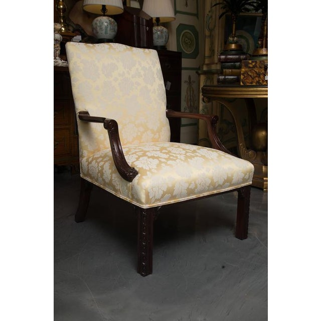 This is a stately and elegant pair of English mahogany library chairs with fully upholstered back and seat, flanked by...