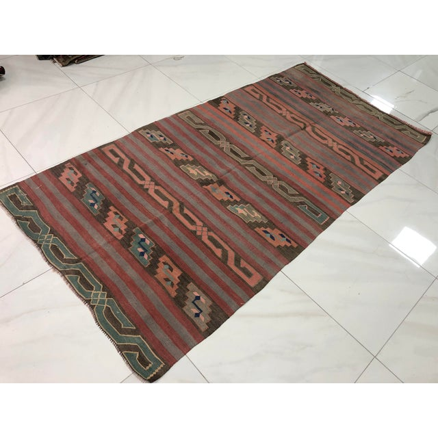 This is a vintage Turkish anatolian Kilim rug from the 1960s. The piece was hand-woven.