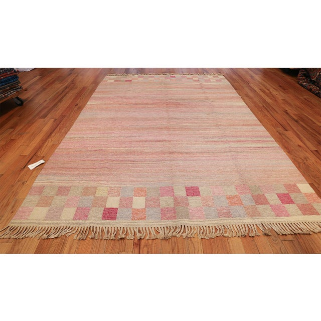 This flat-woven Kilim combines soft pinks, rose-red, oatmeal and ashy browns in a subtle variegated pattern accented by...