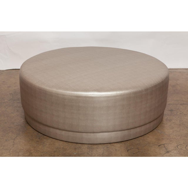 Chic pair of matching round ottomans newly upholstered in a rich textured metallic silver/gold fabric with a gorgeous...