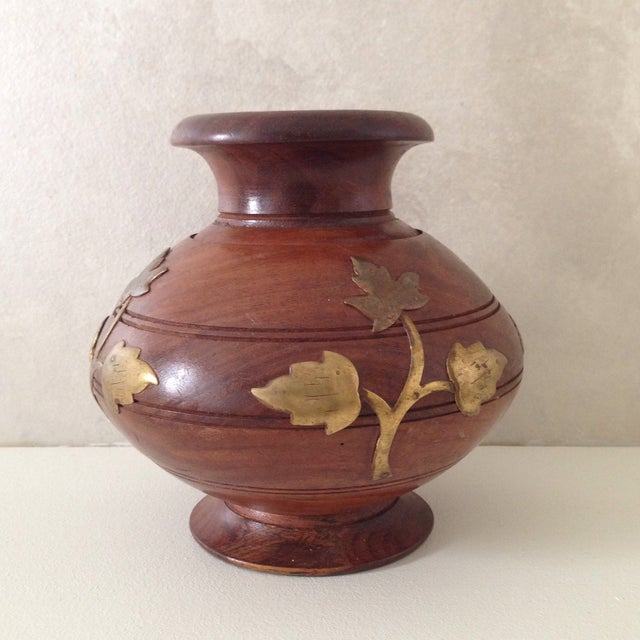 A beautifully embellished wooden pot or vase with lovely brass foliage details on it. Makes a great decorative piece by...