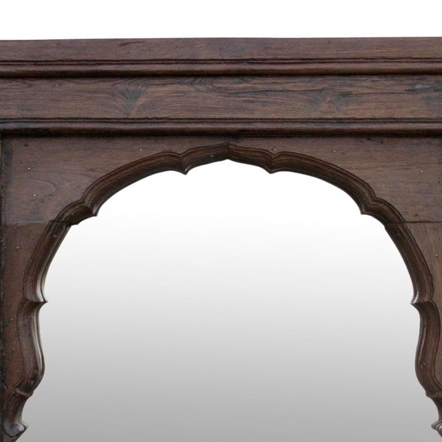 Curated by repurposing a window from an old Haveli in Gujrat, this mirror features intricate hand carved designs in teak...