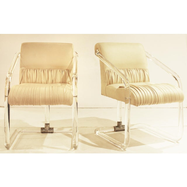 """Pair of signed """"Lion in Frost"""" lucite and chrome arm-chairs upholstered in channel tufted and ruched cream leather."""
