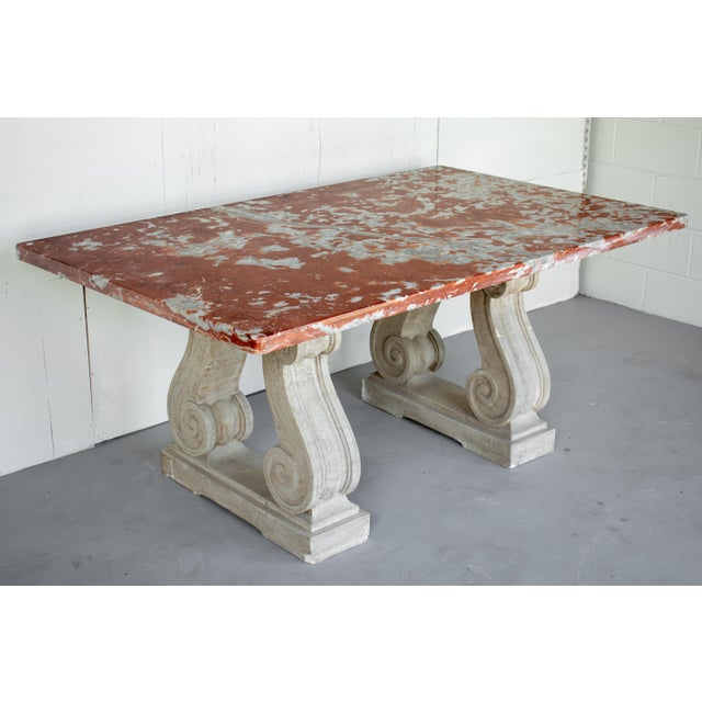 A French center table with a marble top supported by a pair of cast concrete neoclassical scroll form pedestals. Beautiful...