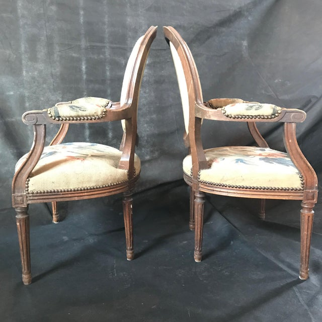 A gorgeous pair of early 19th century French walnut tapestry chairs with original tapestry fabric and plaid upholstery on...