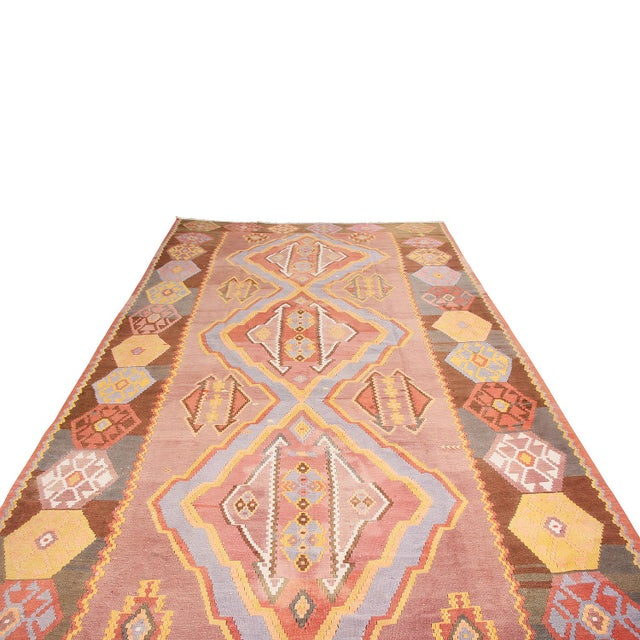 Hand woven in high-quality wool originating from Turkey between 1930-1940, this vintage flat-woven Kilim rug hosts a very...