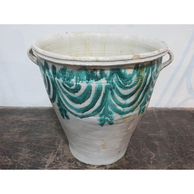 Found in Spain while on a European buying trip. This pot has a white glaze with vibrant hand painted green swag designs....