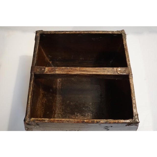 Antique Chinese rice box or bucket featuring a distressed, lacquered finish and metal joinery. This piece appears to have...
