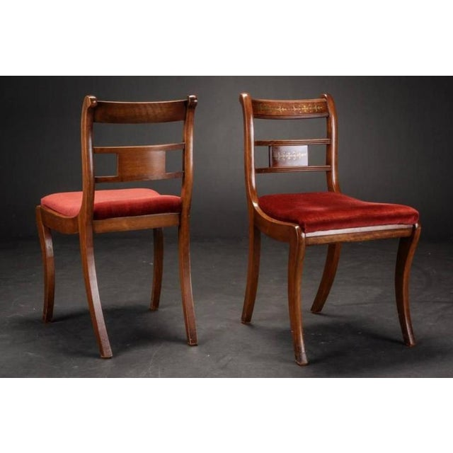 Six chairs made from rosewood and mahogany. They feature back rest with brass inserts. The set has signs of wear and some...