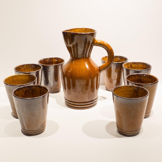 Hand-thrown and glazed earthenware service for eight, comprised of a pitcher and eight cups, from the Poterie du Grand...