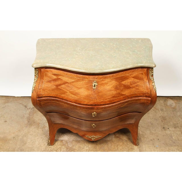 A Swedish Rococo revival Bombay chest. This Rococo Revival chest is covered overall in parquetry, with gilt ormolu. It has...