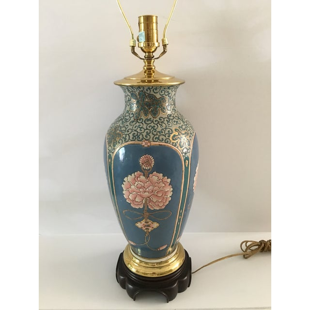Beautiful contemporary Asian inspired Ethan Allen lamp. Blue , pink , green and gold floral motif . Brass cap and rim on a...