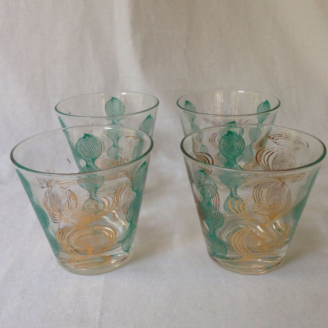 A beautiful set of four vintage bar glasses with a repeating gold and blue pattern. There is some gilt loss, but overall...