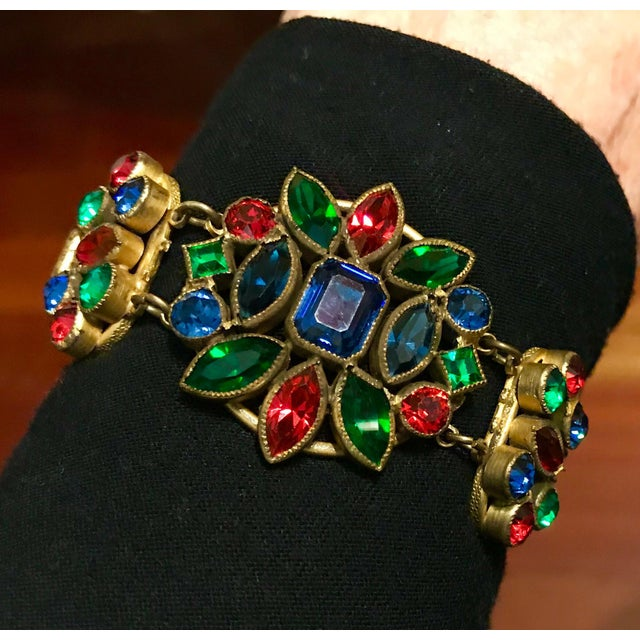 Circa 1930s Czech brass and gold tone metal multi chain bracelet. The top is bezel set with multi-shaped and faceted jewel...