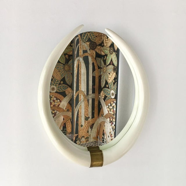 A Faux Tusk Ivory Lacquered Mirror with Brass Mount 1970s NB: These items are subject to a further discount over and above...