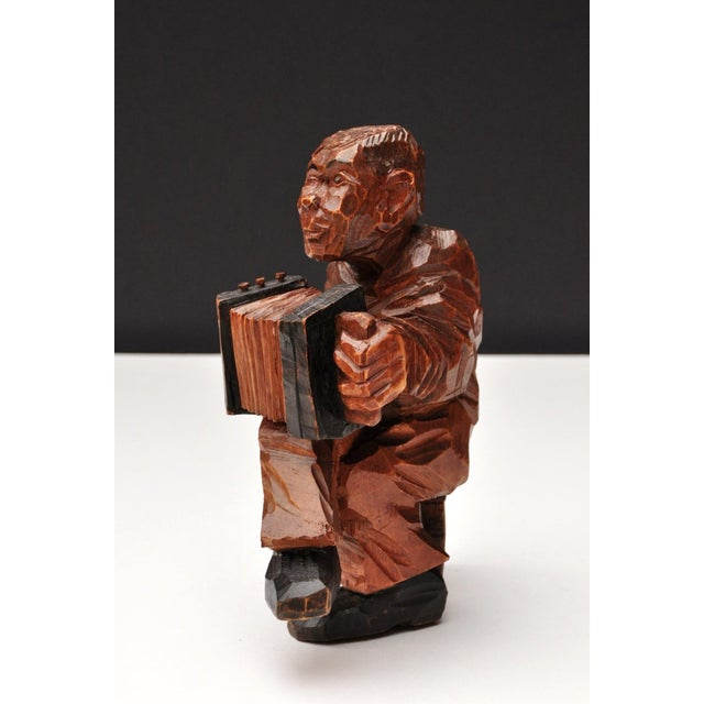 Finely tuned figure in chiseled hardwood holding an accordion. The figure is able to sit comfortably on a single foot, so...