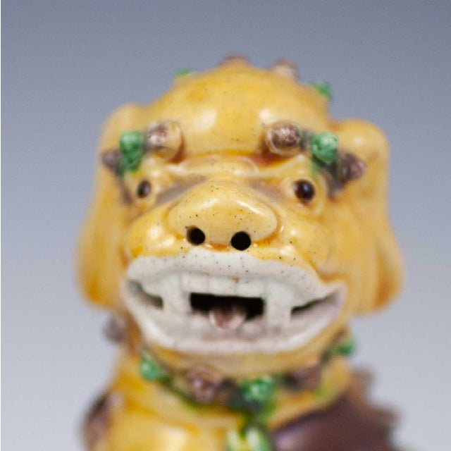 """A pair of pottery Sancai glazed ceramic foo dogs.Garnished with yellow, green, and purple toned glazes. Marked:""""China""""..."""