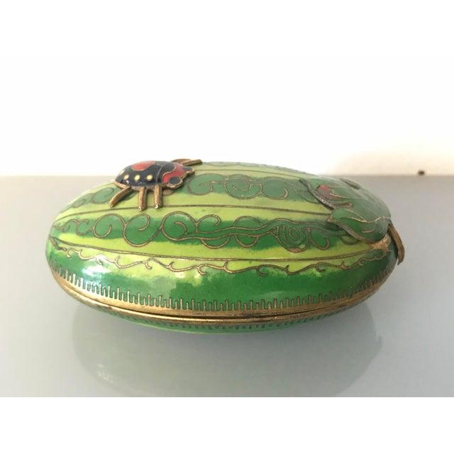 A wonderful enameled box of a ladybug resting on a watermelon. Fantastic details