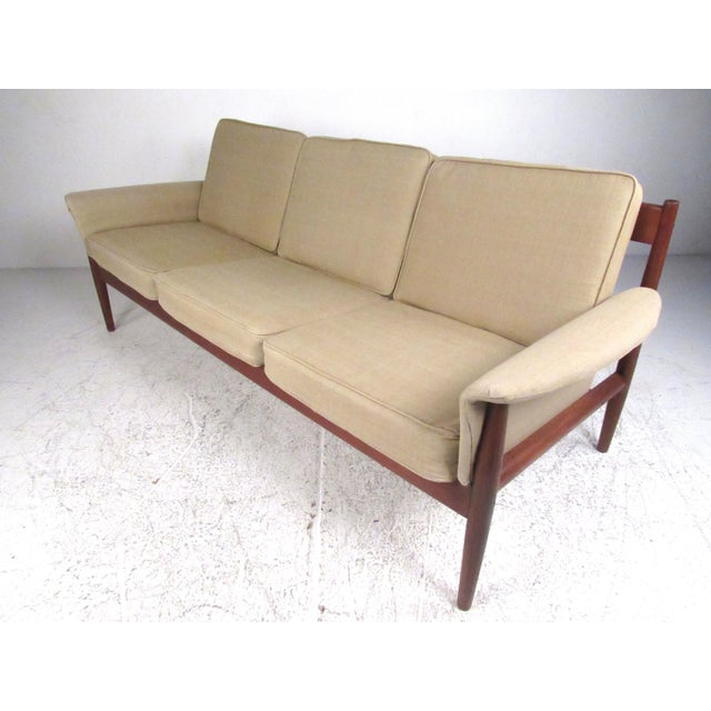 This stylish Mid-Century Modern teak sofa features comfortably upholstered three person seating, with sculpted teak frame...