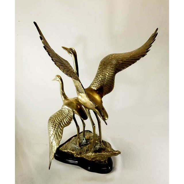 Gorgeous sculpture of 2 cranes / herons standing on a rock with wings open. Sculpture sits on a mahogany shade wood mount....