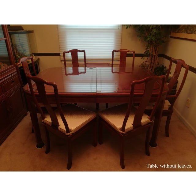 A beautiful cherry-colored rosewood set comprised of an [expandable dining room table + 8 chairs], 2 of which are armed...