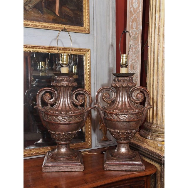 A pair of Italian carved and silver leaf wood lamps in an urn design, metal bobeches, square base. Mid 20th century....
