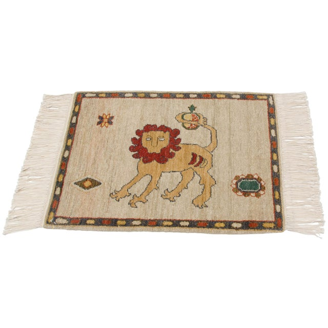 :: Pictorial design motif with a lion bearing a wildly expressive curled mane with its tail in the air, wrapped around...