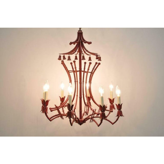 Vintage red painted Italian faux bamboo tole metal chandelier. Item features a unique pagoda frame with non-ringing bell...