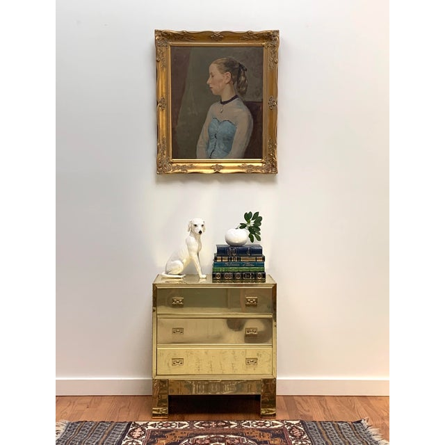 "Portrait of a seated young woman in oil on board in a carved giltwood frame, signed ""Auld 57."" This serene, rendering of a..."
