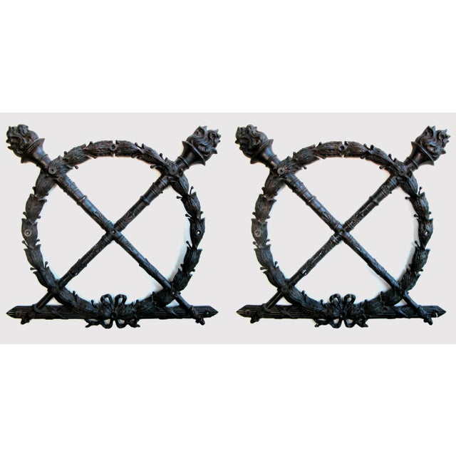 A heraldic pair of FrenchLouis XVI style bronze laurel wreaths; each boldly-scaled wreath adorned with crossing torchieres...