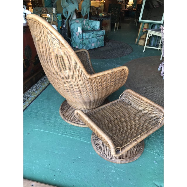 Vintage wicker egg chair and ottoman that swivels and tilts in as found vintage condition. It has cushions but would need...